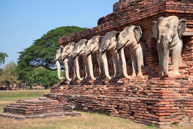 Skulpturer av elefanter på grunden av stupaen av den buddistiska templet av Wat Sorasak Sukhothai Thailand fotografering för bildbyråer