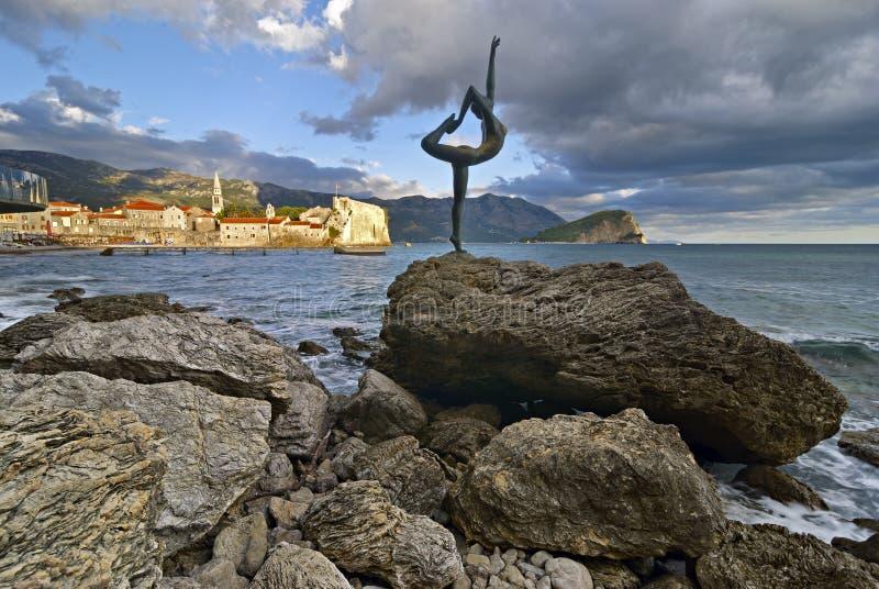 Skulpturflickadans Mot bakgrunden av den gamla staden av Budva royaltyfria bilder