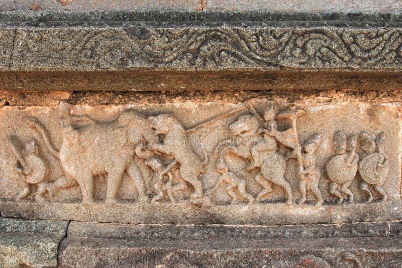 Skulpturvisningjakt av en tiger av män för konung` s, Hampi arkivbild