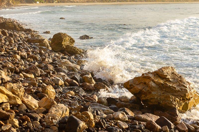 Skumma vågen som bryter på soluppgång med stenig shoreline arkivfoto