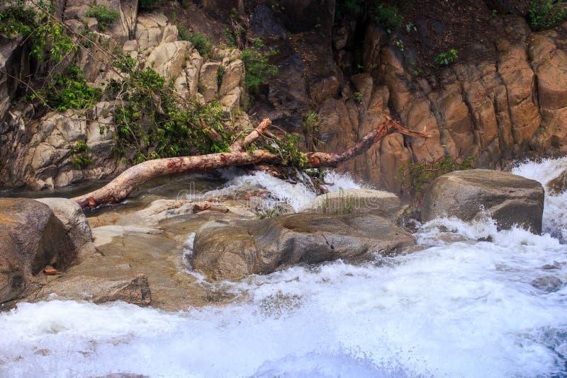 Skummande flodflöde mot bruna stenar arkivbild