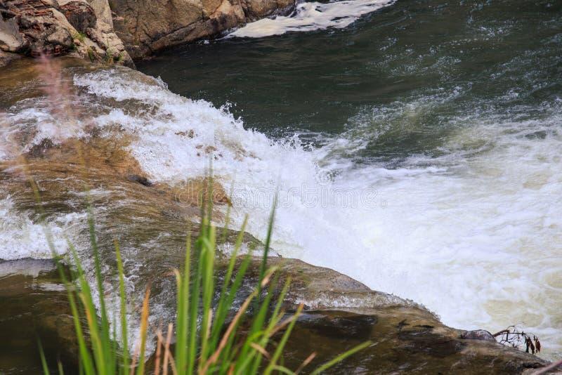 Skummande flodflöde mot bruna stenar arkivfoto