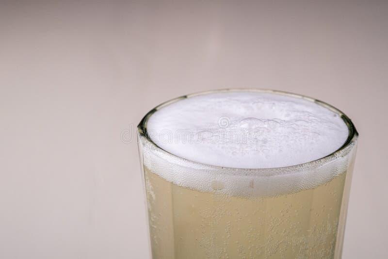 Skummig kvass för ny kall drinkdryck i fasetterat exponeringsglas på vit träbakgrund arkivbilder