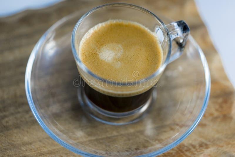 Skummigt svart kaffe i exponeringsglas rånar på tabellen royaltyfri bild