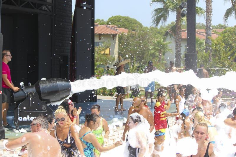 Skumparti på stranden Många personer i skumet royaltyfria bilder