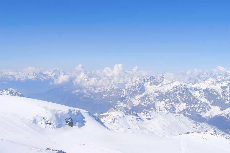 Skumulowanie cumulusu chmury między śnieżnymi szczytami w Szwajcarskich Alps zdjęcie stock