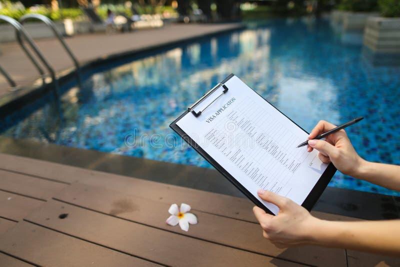 Skupia się na dokumencie, dziewczyna pełnie opróżniają papier na tle basen obraz royalty free