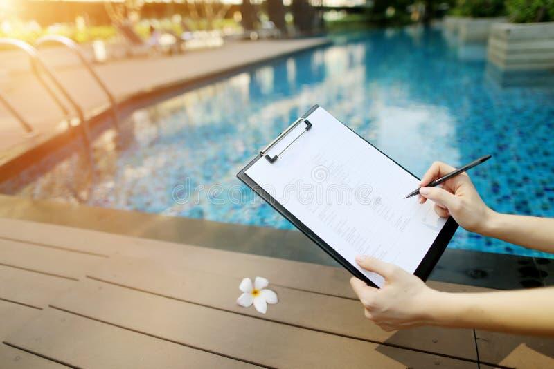 Skupia się na dokumencie, dziewczyna pełnie opróżniają papier na tle basen Przód używać z Otwartym chrzcielnica licencja obraz stock