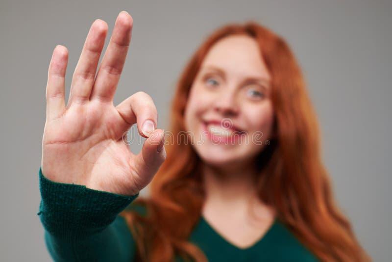 Skupia się na gescie dawać rudzielec kobietą sukces zdjęcie royalty free