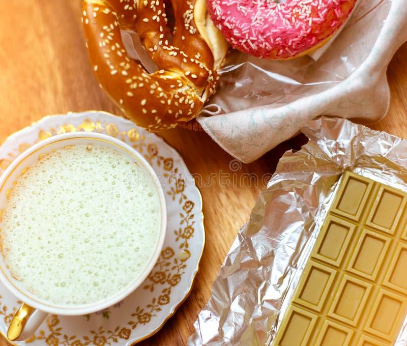 Skupia się na zielonej czekoladzie z Chińską matcha herbatą, antykwarską porcelany filiżanką z batożącą śmietanką i preclami z lu zdjęcie stock