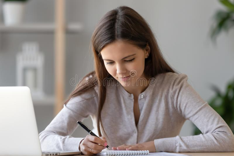 Skupiająca się kobieta pisze zawiadomieniu przepustka egzamin, używać laptop, przygotowywa obraz royalty free