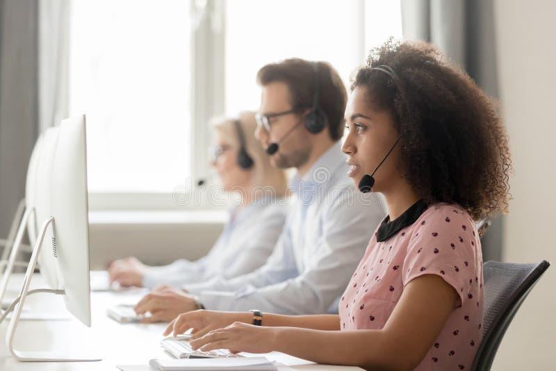 Skupiający się afrykański centrum telefoniczne operatora ordynacyjny klient patrzeje komputer zdjęcia stock