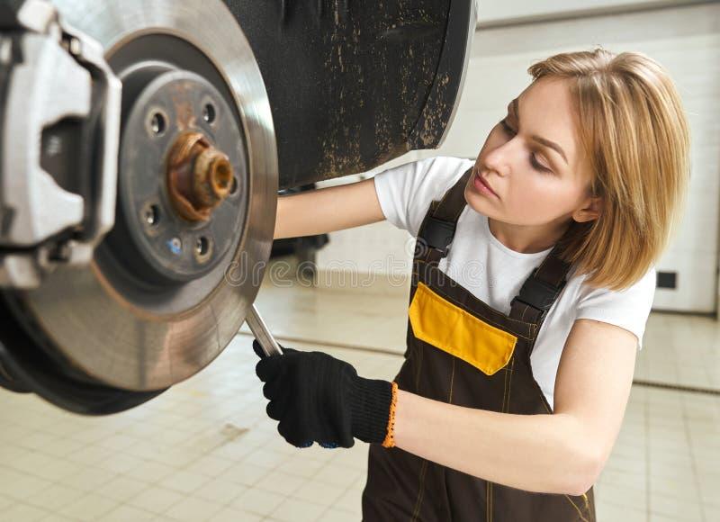 Skupiająca się żeńska mechanika odmieniania opona samochód w warsztacie zdjęcie stock