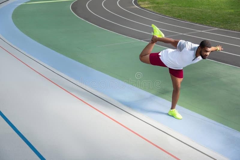 Skupiająca się przystojna młoda męska atleta rozciąga jego iść na piechotę zdjęcia royalty free
