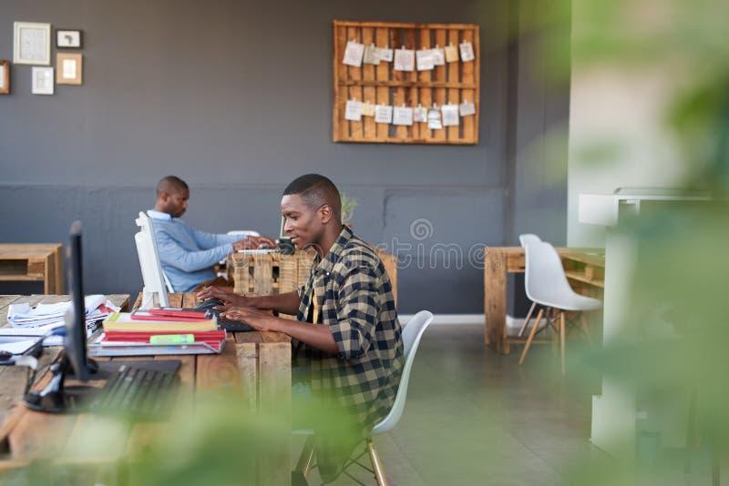 Skupiający się Afrykańscy biznesmeni mocno przy pracą w nowożytnym biurze zdjęcia royalty free