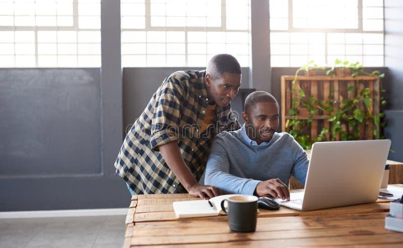 Skupiający się Afrykańscy biznesmeni używa laptop przy biurowym biurkiem zdjęcie stock
