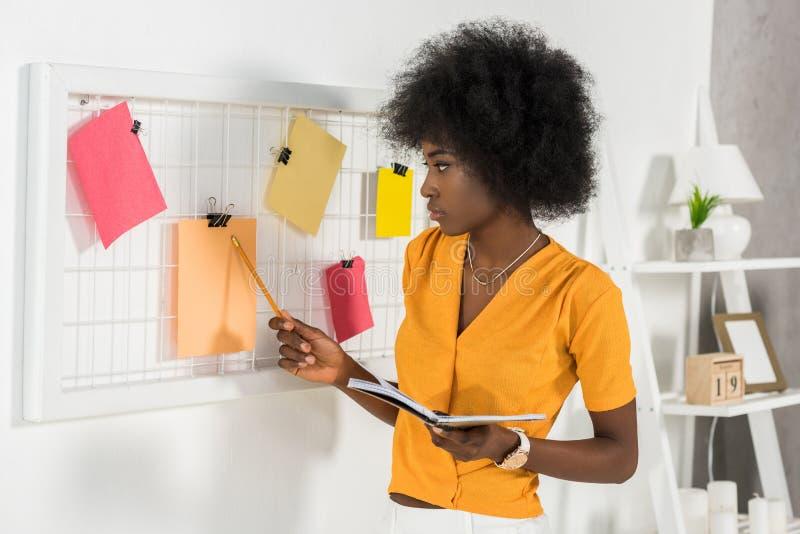 skupiający się amerykanin afrykańskiego pochodzenia freelancer wskazuje przy deską z pustymi papierami z notatnikiem obrazy royalty free
