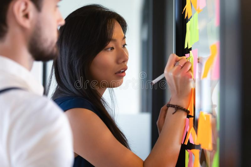 Skupiający się azjatykci bizneswoman pisze na kleistych notatkach na szkle zdjęcie royalty free