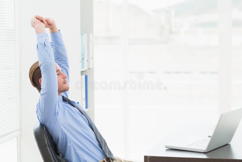 Skupiający się biznesmena rozciąganie przy jego biurkiem zdjęcie stock