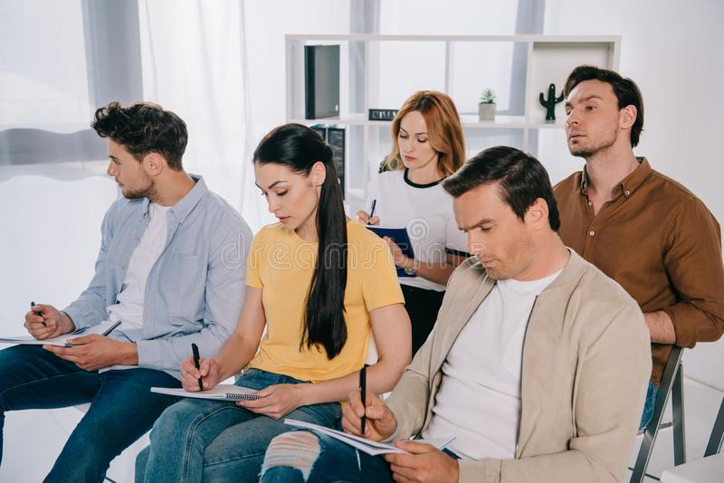 skupiający się bizneswomany w przypadkowej odzieży robi notatkom w notatnikach na biznesowym szkoleniu i biznesmeni fotografia royalty free