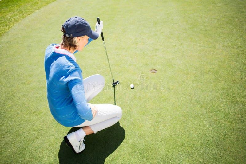 Skupiający się dama golfisty klęczenie na kładzenie zieleni fotografia stock