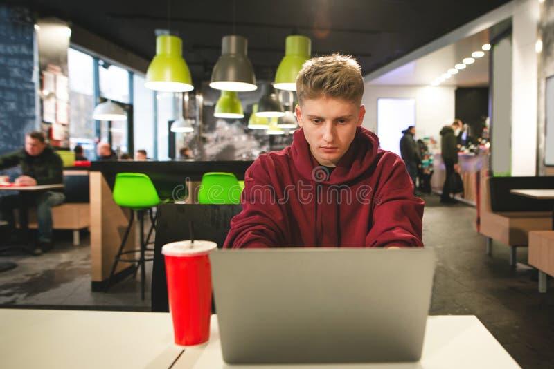 Skupiający się faceta freelancer pracuje na laptopie w fast food kawiarni, skupia się na ekranie zdjęcie royalty free