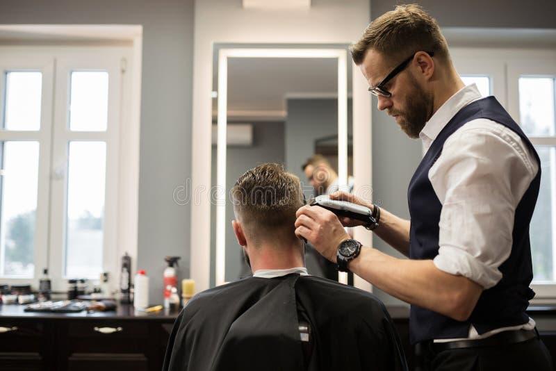Skupiający się fryzjer męski ma klienta włosy zdjęcia stock