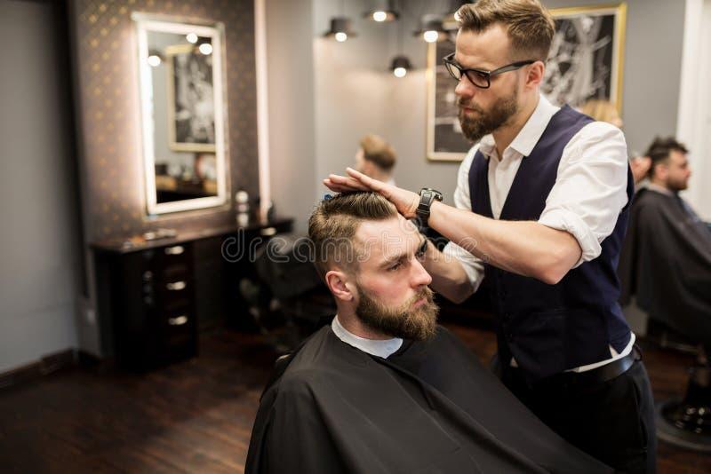 Skupiający się fryzjer męski pracuje na klienta włosy obrazy royalty free