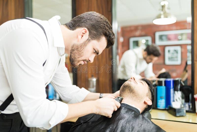 Skupiający się fryzjera męskiego arymażu klienta ` s Twarzowy włosy W salonie fotografia royalty free