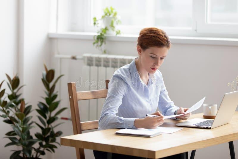 Skupiający się kobiety obsiadanie przy biurkiem pracuje sprawdzać dane w dokumentach zdjęcia stock