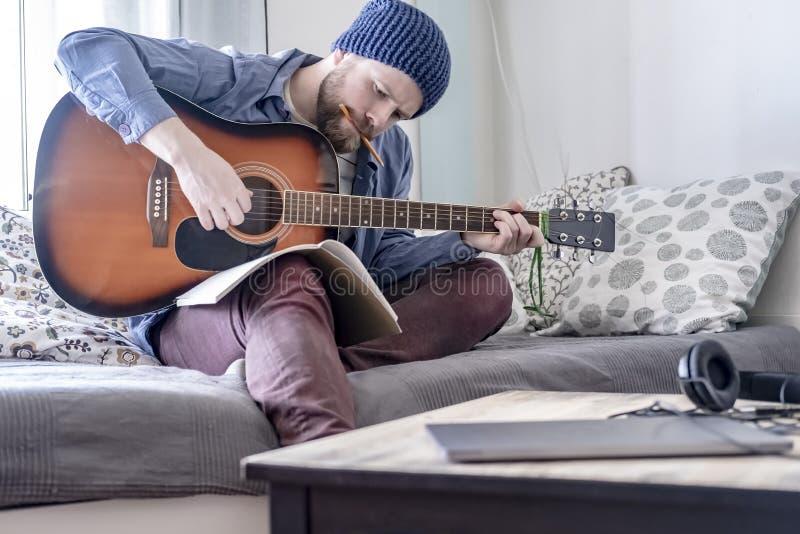Skupiający się kompozytor bawić się pisać muzykę na gitarze akustycznej podczas gdy patrzejący ołówkiem w jego usta i z notatnika zdjęcia royalty free