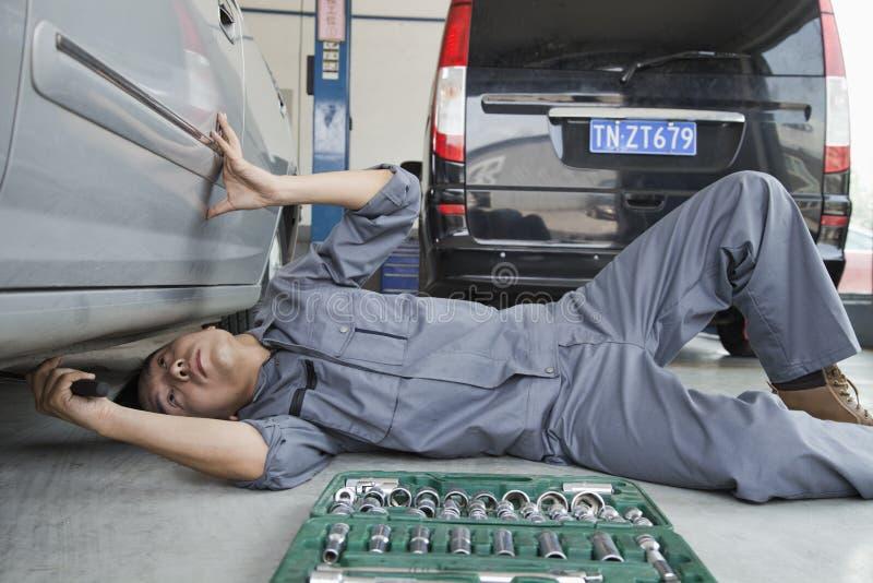 Skupiający się mechanik Pracuje pod spodem samochodu zdjęcia royalty free