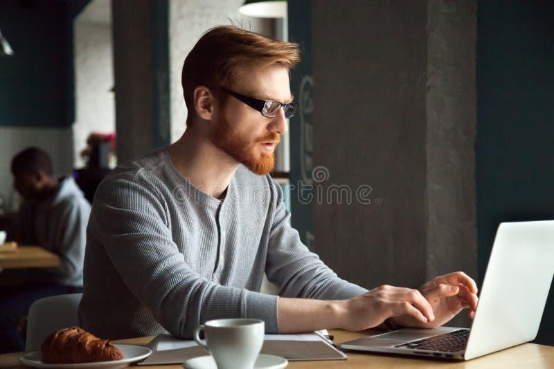 Skupiający się millennial rudzielec mężczyzna używa laptopu obsiadanie przy cukiernianym tabl fotografia stock