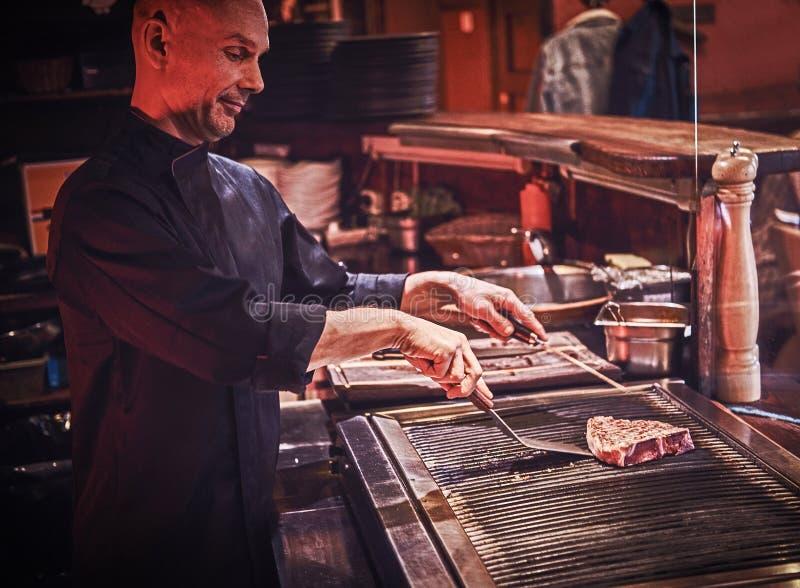 Skupiający się mistrzowski szef kuchni jest ubranym jednolitego kulinarnego wyśmienicie wołowina stek na kuchni w restauracji obrazy royalty free