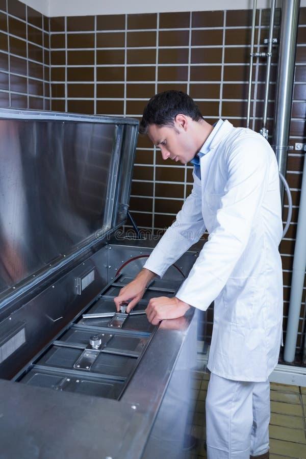 Skupiający się piwowar pracuje przy maszyną zdjęcia stock