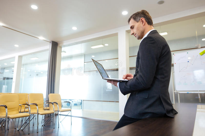 Skupiający się poważny biznesmena narządzanie dla prezentaci używać laptop obrazy stock