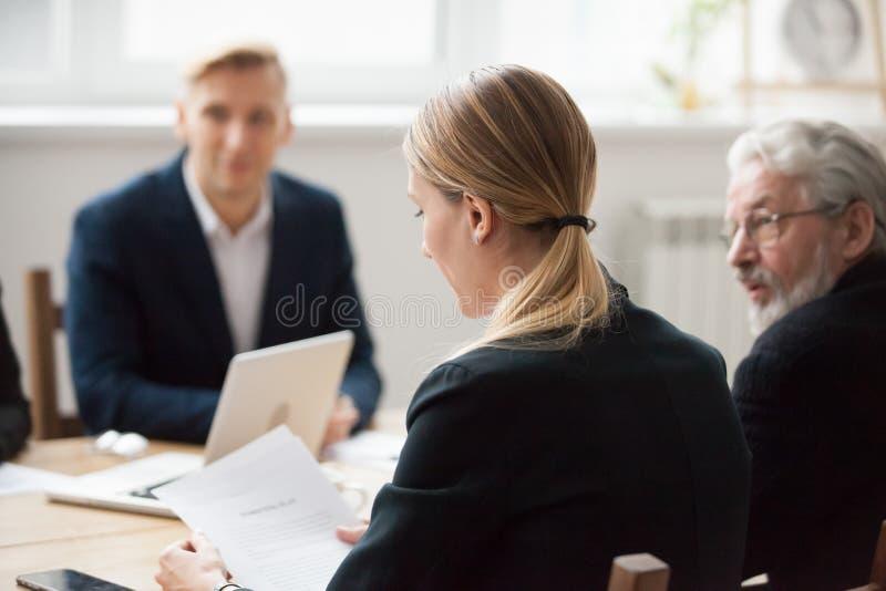 Skupiający się poważny bizneswomanu czytania dokument przy spotkaniem grupowym obraz stock