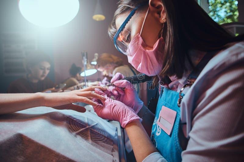 Skupiaj?cy si? skrz?tny manicurzysta pracuje przy jej miejsce pracy przy manicure'u salonem zdjęcia stock