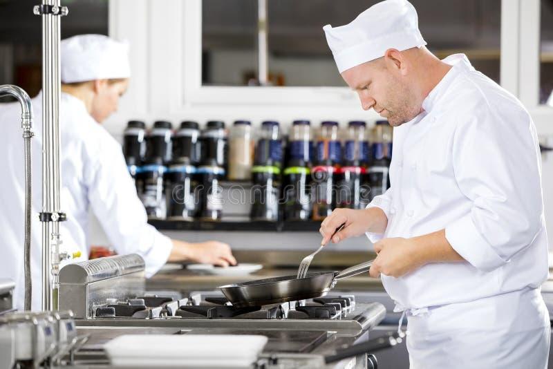 Skupiający się szefowie kuchni robią jedzeniu w fachowej kuchni zdjęcie royalty free