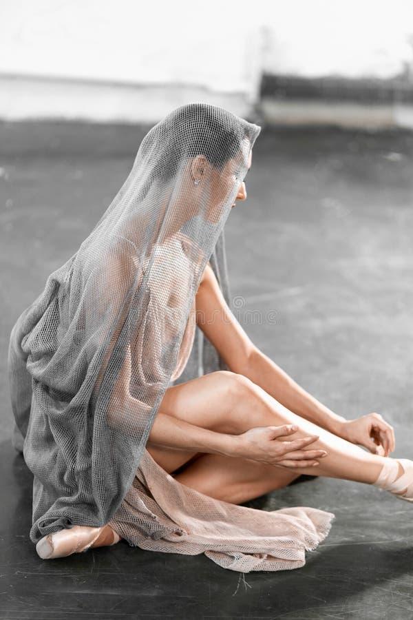 Skupiaj?cy si? i spokojny baleriny k?adzenie na pointe butach siedzi na popielatej kamiennej pod?odze zdjęcie royalty free