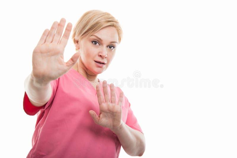 Skurar den bärande rosa färgen för den attraktiva kvinnliga sjuksköterskan att se skrämd arkivfoton