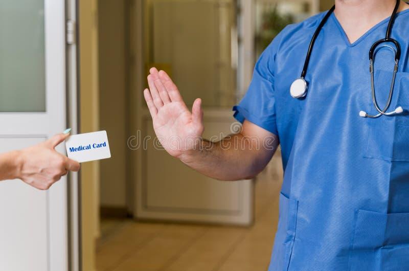 Skurar den manliga doktorn för den mellersta åldern in att vägra det medicinska kortet royaltyfri foto