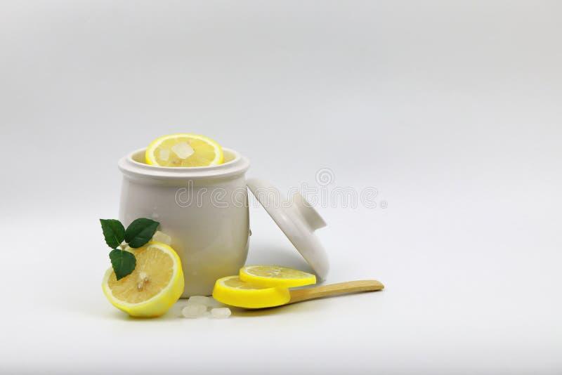 Skurar den ny guling skivade citronen, och crystal socker vaggar det godismintkaramellen och bladet i den vita isolerad vit bakgr royaltyfri fotografi