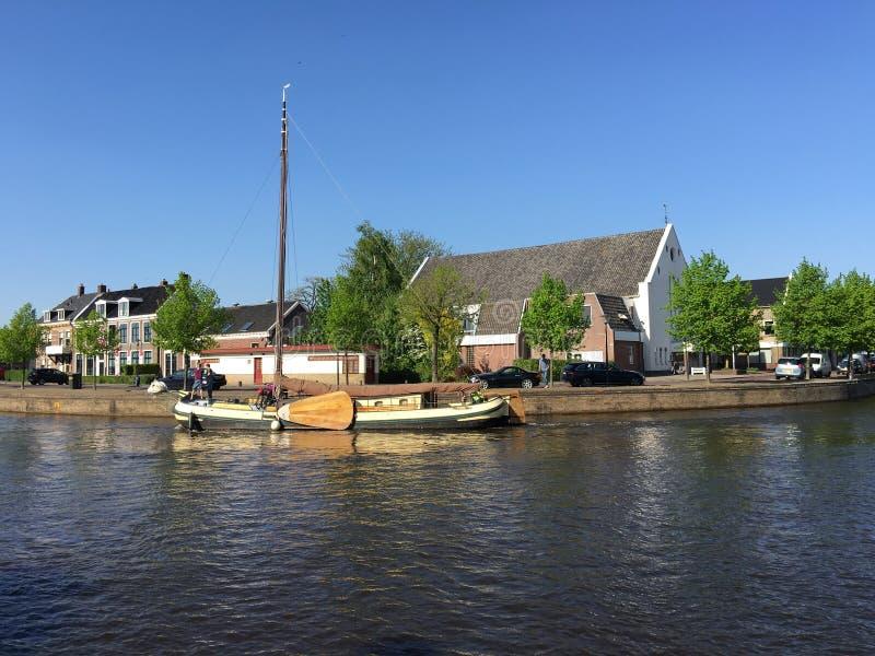 Skutsje in the Prinsengracht. Skutsje sailing through the Prinsengracht with the waterpoort in the background in Sneek, Friesland The Netherlands stock photos