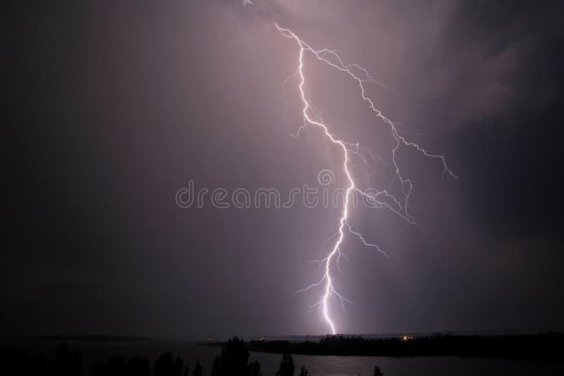 ?skv?der- och blixtslag ?ver floden p? natten arkivbild
