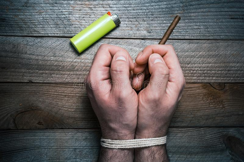 Skwitowany dymienia pojęcie Z 2 Wiązać rękami Na Drewnianym stole Obok zapalniczki Prawa ręka Trzyma papieros obrazy royalty free
