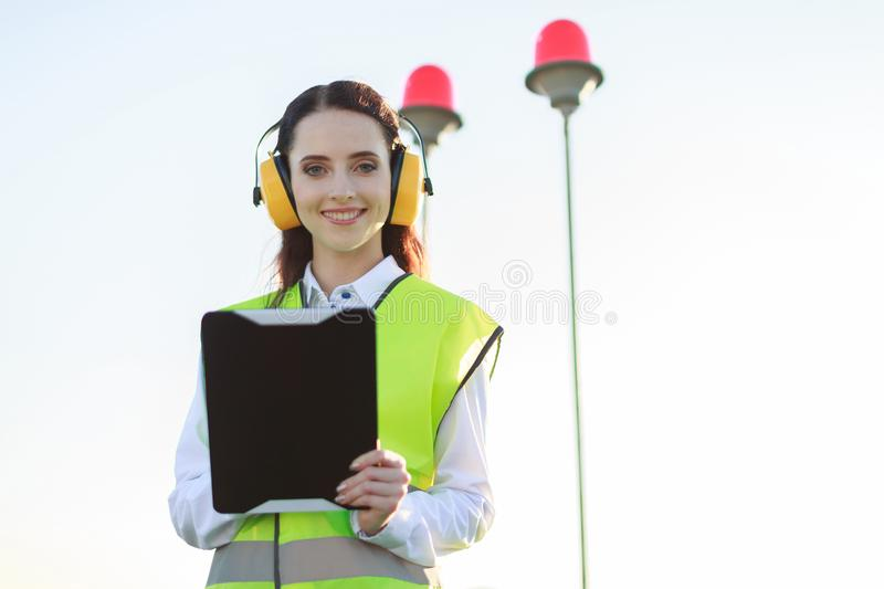 Attractive young woman in green west and earmuffs stand on roof, hold tablet royalty free stock photography