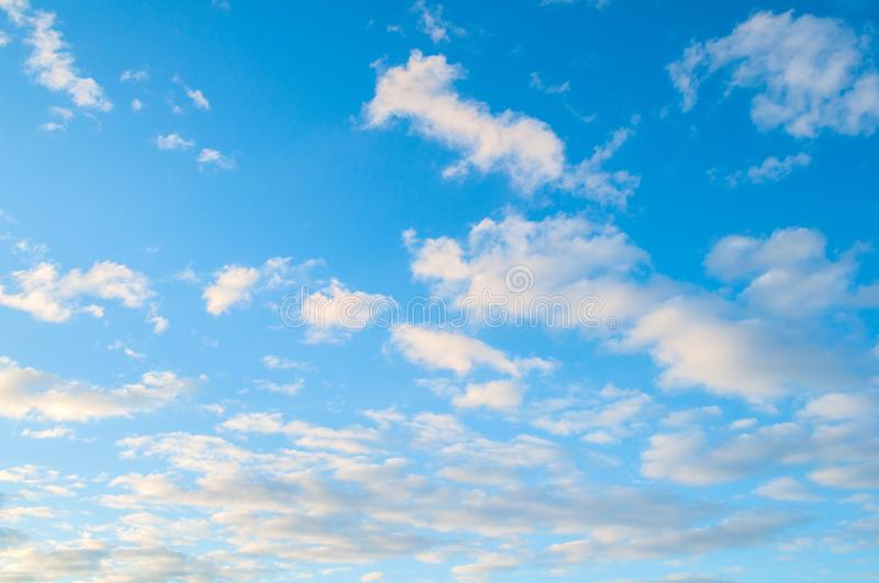 Sky background. Blue sky landscape with sunset clouds lit by evening sunset light. Sky background. Blue sky landscape with dramatic sundown clouds lit by evening royalty free stock images