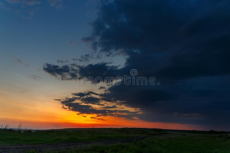 The sky with bright clouds lit by the sun after sunset over the field. The sky with bright clouds lit by the sun after sunset over the field royalty free stock images