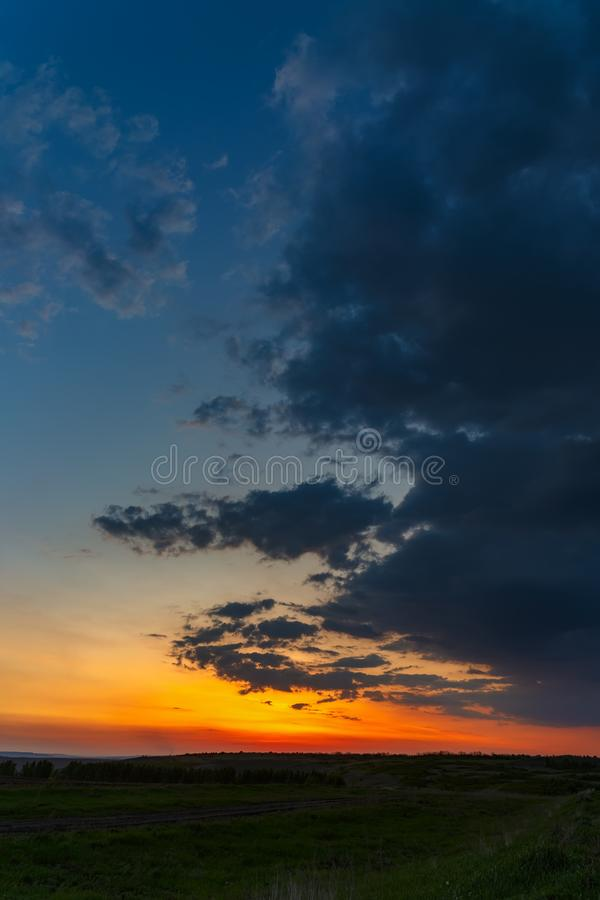 The sky with bright clouds lit by the sun after sunset over the field.  stock photography